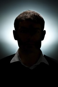 A portrait of a man lit with only a hair light and a background light.